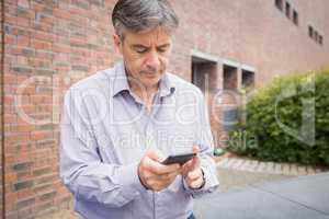 Professor using mobile phone in campus