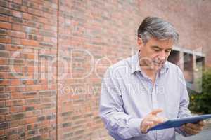 Professor using digital tablet in campus