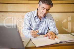 Professor writing in book at desk