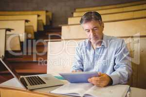 Professor sitting at desk using digital tablet