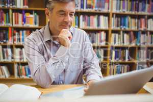 Professor sitting at desk using laptop
