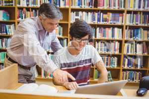Professor assisting a student with laptop