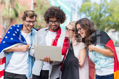 Friends holding national flag and using laptop