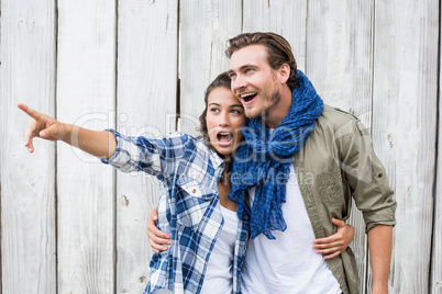 Young woman standing with man pointing upward
