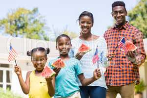 Happy family showing usa flag and eating watermelon