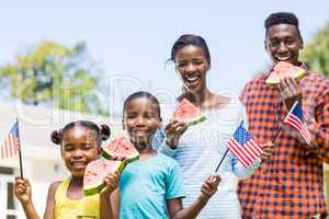 Happy family eating watermelon and showing usa flag
