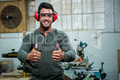 Carpenter is posing with his thumbs up and his protection equipm