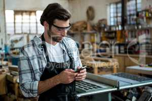 Carpenter texting someone and wearing protective glasses