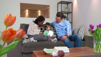 Multiethnic Couple Reading Book To Child Man Woman Daughter Baby