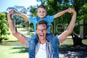 Happy father carrying his son on the shoulder in the park