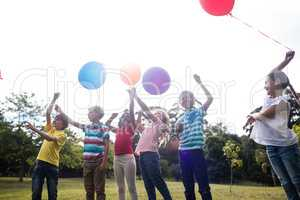 Happy children playing with balloons in the park