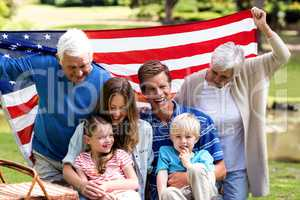 Multi-generation family holding american flag in the park