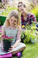 Girl sitting in garden with flower pot