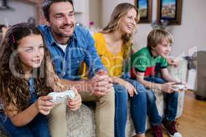 Family sitting on sofa and playing video game