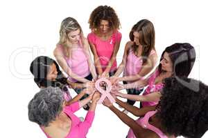 Women in pink outfits standing in a circle for breast cancer awa