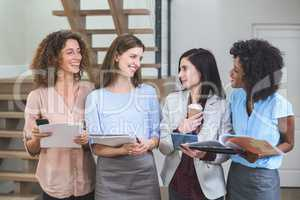 Female business colleagues standing together with file and digit