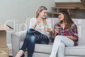 Two beautiful woman sitting on sofa and having pizza