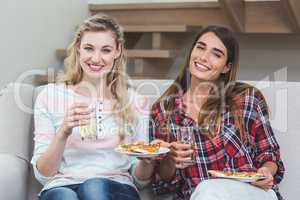 Two beautiful women sitting on sofa and having pizza