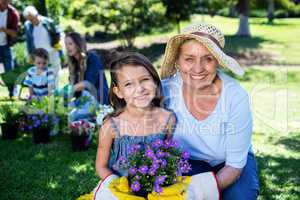Grandmother and granddaughter holding a flower pot while gardeni