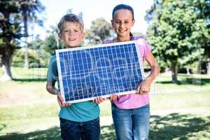 Siblings holding a solar panel