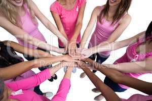 Women in pink outfits joining in a circle for breast cancer awar