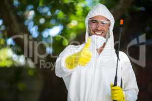 Man showing thumbs up while holding insecticide sprayer