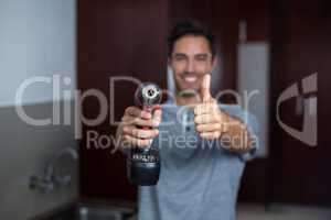 Smiling man showing thumbs up while holding cordless hand drill