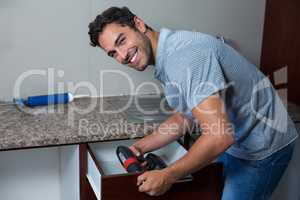 Portrait of happy man using cordless hand drill
