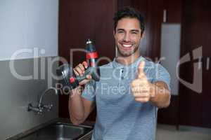 Happy man showing thumbs up while holding cordless hand drill