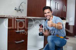 Cheerful man showing thumbs up while using cordless hand drill