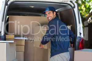 Happy delivery man loading cardboard box in van