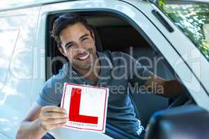 Portrait of happy man with leaning sign