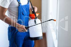 Midsection of pest control worker with sprayer
