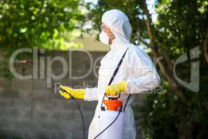 Side view of worker using pesticide in back yard