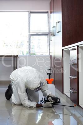 Pest control man spraying pesticide under the cabinet