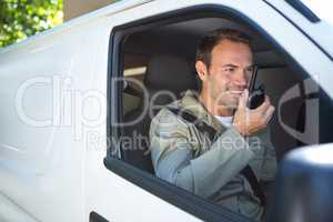 Delivery driver talking on walkie-talkie