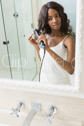 Reflection of young woman straightening hair