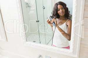 Reflection of young woman straightening hai