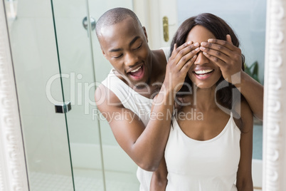 Reflection of young man covering womans eyes