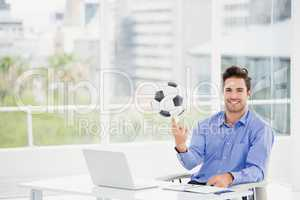 Businessman spinning a football on his finger