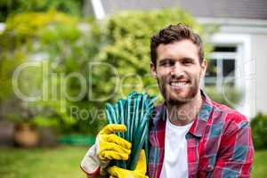 Smiling man carrying garden hose in backyard