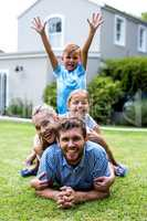 Boy with arms raised with family in yard