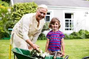 Garndmother and boy with flower pots in wheelbarrow