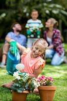 Girl watering flower pots in yard