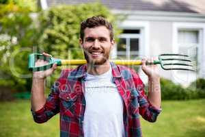 Smiling man carrying rake while standing in yard