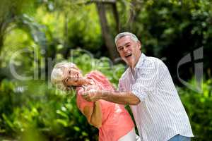 Senior couple enjoying while dancing in yard