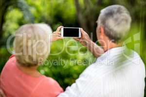 Senior couple taking selfie in yard