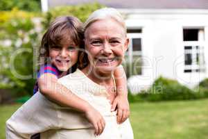 Granny piggybacking grandson in yard