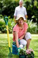Senior woman with gardening equipment in yard