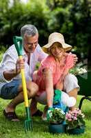 Smiling senior couple with gardening equipment at yard